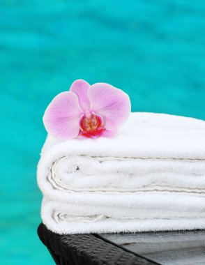 Clean towel with orchid poolside