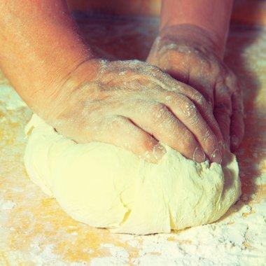 Women's hands knead the dough