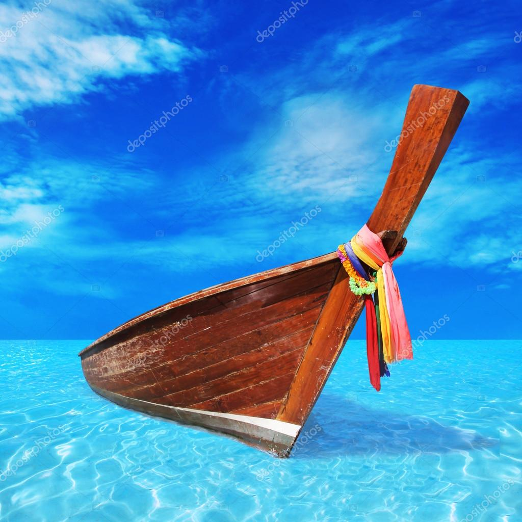 wooden boat in the blue sea