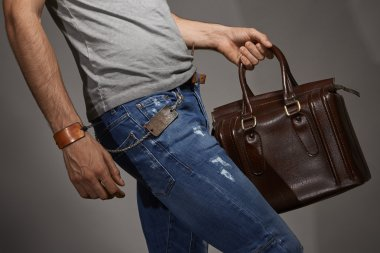Young man carrying a leather bag