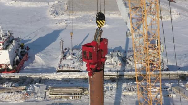 Sabetta, Region Tjumen, Russland - 25. März 2021: Der Rammarbeiter fährt den Ramm in die Erde. Bewölkt mit leichtem Schnee.