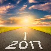 Prázdné rovná cesta k nadcházející 2017 při západu slunce