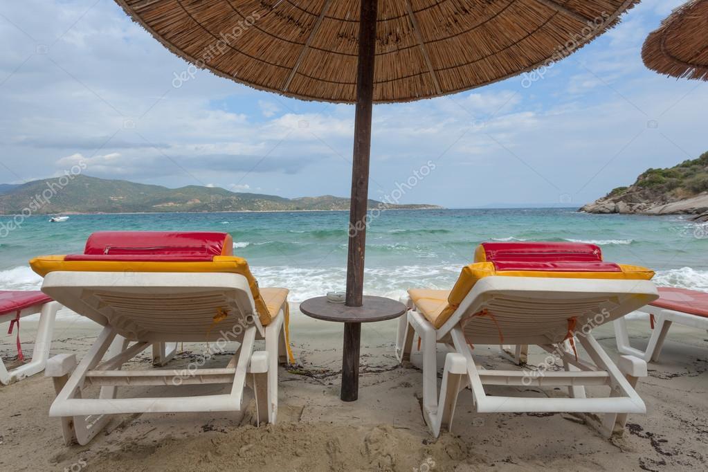 Coppia di sedie a sdraio sulla spiaggia con ombrellone di paglia