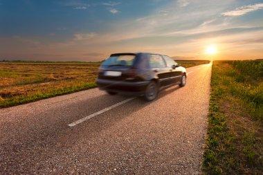 Black car in motion blur on open road