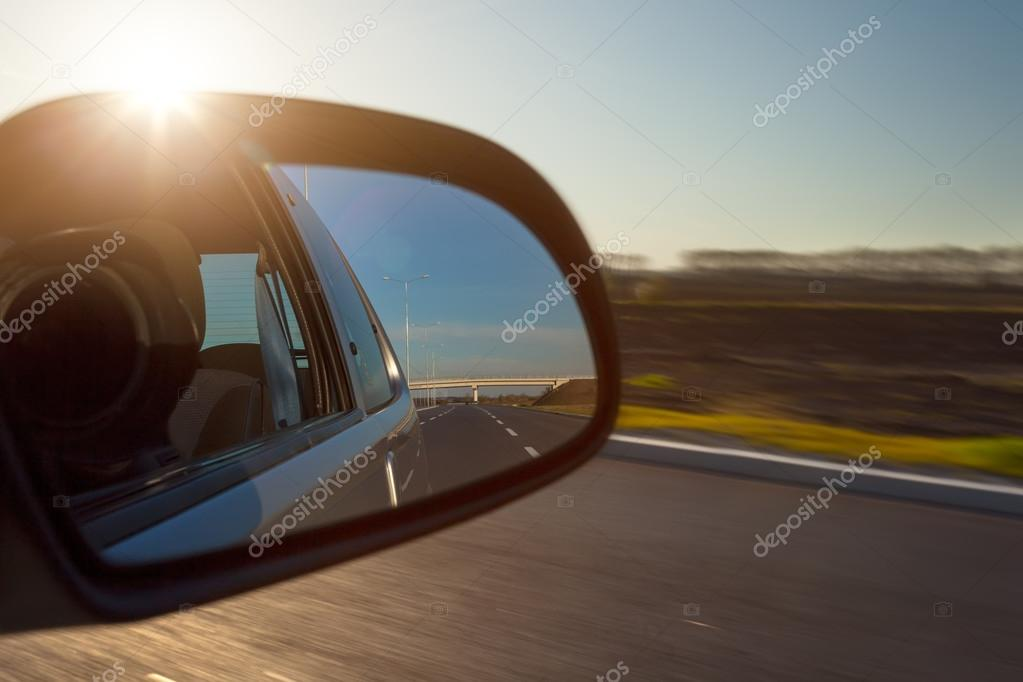 Rearview mirror and the setting sun from car