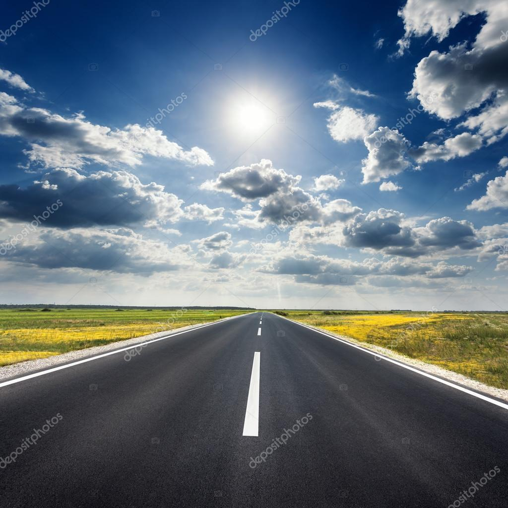 Driving on straight asphalt road towards the sun