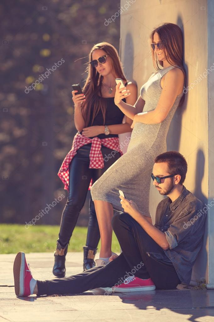 Group of young hipsters chatting by phones