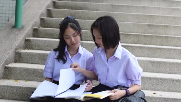 Cute Asian Thai high schoolgirls student couple in school uniform sit on the stairway discussing and arguing homework or exam together.
