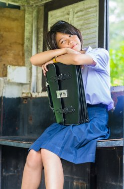 Cute Thai schoolgirl in uniform is daydreaming in an old bus stop. She is hugging her school bag.