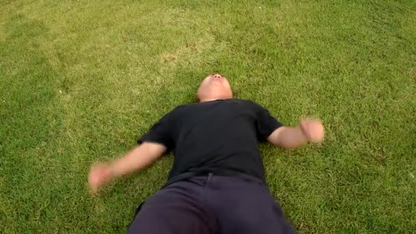 A fat bald head Asian Thai man is acting struggling like a spoil child having seizures with angry raging face or having mental illness on green grass in 1920x1080 HD quality. Psychiatrist therapy is needed.