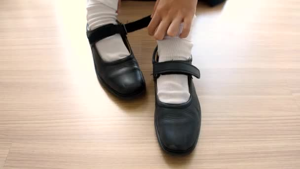 9d8ce3288658 Asian Thai schoolgirl student in high school uniform is wearing her black  leather shoes in cute education fashion design on the wooden floor  classroom in ...