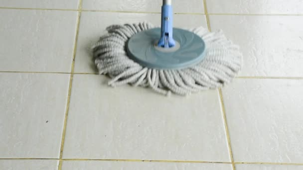 A moving cloth mop is used to clean a white tile floor. Cloth mop is a housekeeping housework tool for housewife and janitor to brush sweep or polish dirt and liquid of the indoor building floor. (1920x1080 HD)