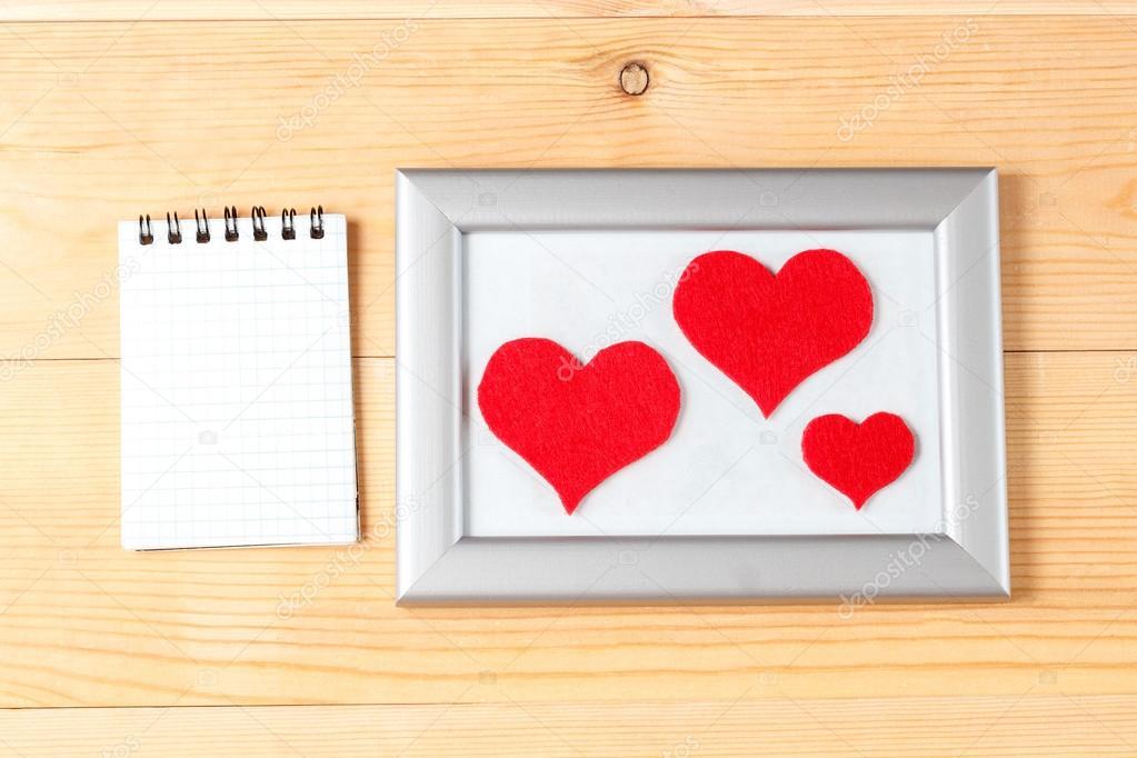 Bilderrahmen, Grußkarte und handgefertigte Herzen über hölzerne ...