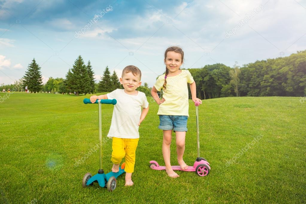 Two boy and a girl standing on the summer green field.