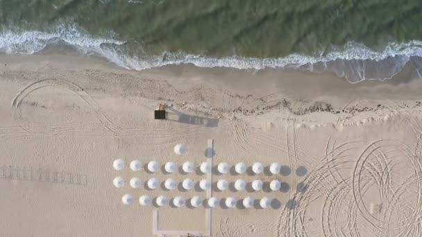 Statische Luftaufnahmen Drohne Video Drone Draufsicht leeren stürmischen Strand mit Sonnenschirmen und Lifeguard Tower Lifeguard _ Tower. Grafik Schatten auf dem Sand. Autorallye-Strecke. Entspannter Blick von oben auf tobendes Meer