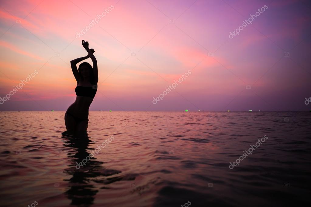 Beautiful sporty feminine silhouette. evening swimming