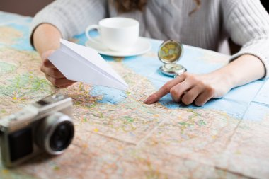 map with a paper airplane, compass and camera and visualises his desire to travel