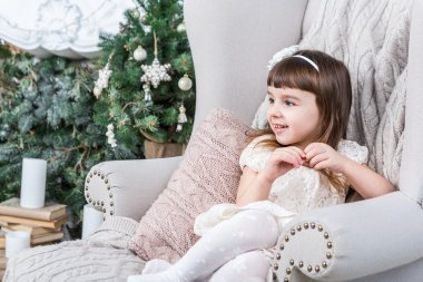 Happy little girl sits comfortably in a light beige home chair.