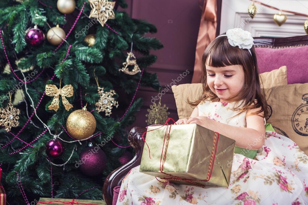 5 Jahre altes Mädchen öffnen eine goldene Verpackung mit einem ...