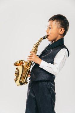 six years old boy plays saxophone at studio