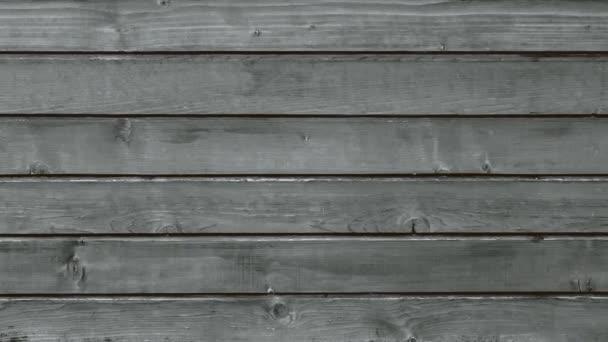 Starý šedý dřevěný plot z prken, spálený na slunci, panorama struktury prastarého dřeva.