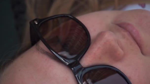 Nahaufnahme des Gesichts eines jungen blonden Mädchens mit Sonnenbrille, ohne Filter, ohne Make-up,