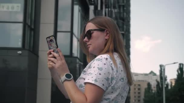 young married girl in glasses makes a photo video on phone against the background of new high house