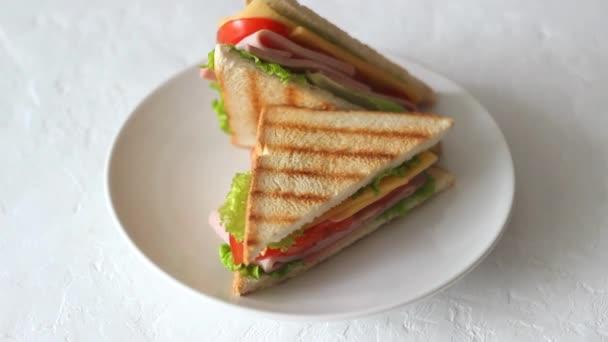 Szendvics salátával, paradicsommal, sonkával és sajttal. Amerikai konyha. Gyors kaja. Főzés.