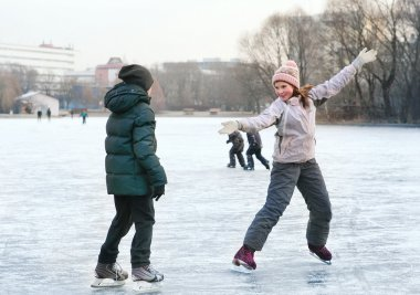 beautiful preteen girl figure skating in open winter skating rin