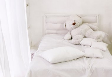 white room corner with bed teddy bear and window with white curt