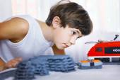 Preteen handsome boy play with meccano toy train and railway sta