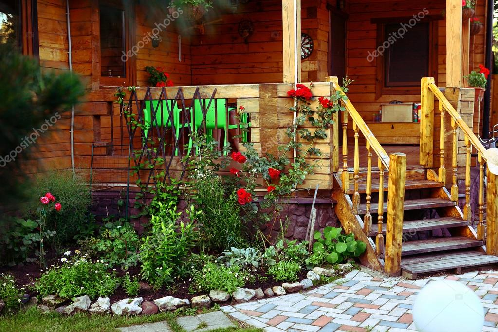 wooden cottage house porch and  tile path in the summer blossoming garden
