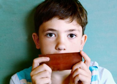 preteen handsome boy with chocolate piece isolated on blue