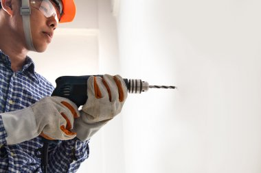 Builder or worker drilling with a machine or drill