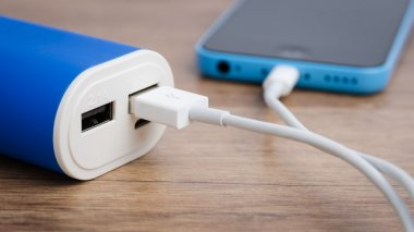 Charging a smartphone from powerbank on wooden table