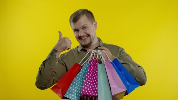 Muž ukazující nápis Černý pátek na nákupních taškách, usmívající se, spokojen s nízkými cenami