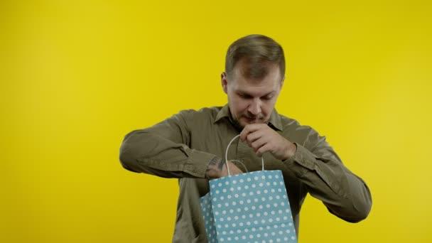 Mann zeigt bis zu 70 Prozent Rabatt aus Einkaufstasche, jubelt über Rabatte, niedrige Preise