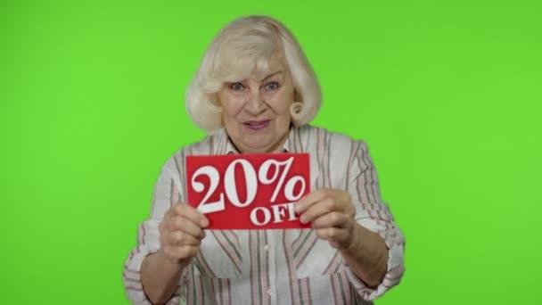 Usmívající se babička ukazující 20% slevu na nápisy, radující se z dobrých slev, nízké ceny