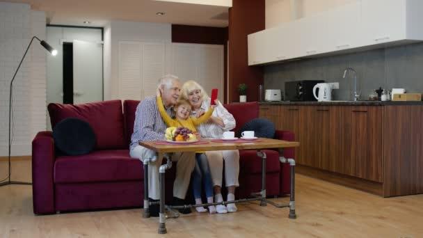 Starší pár prarodiče s dětskou vnučkou dělat selfie fotky společně na mobilním telefonu