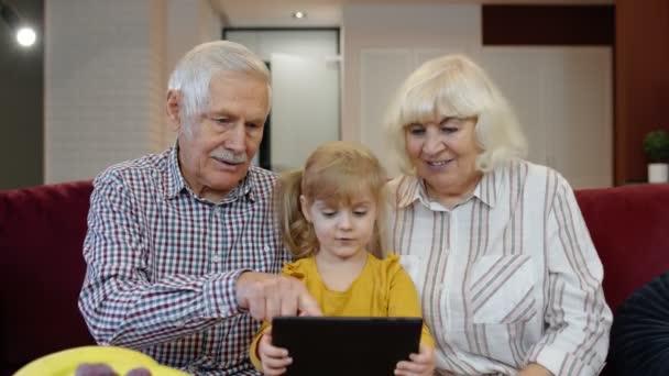 Mädchen zeigt Großeltern etwas im Laptop, Senioren-Paar lernt Umgang mit Tablet