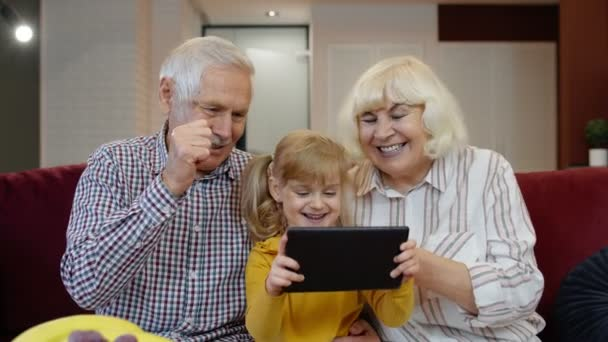 Senior Caucasian couple with cute child girl granddaughter using tablet, watching funny videos