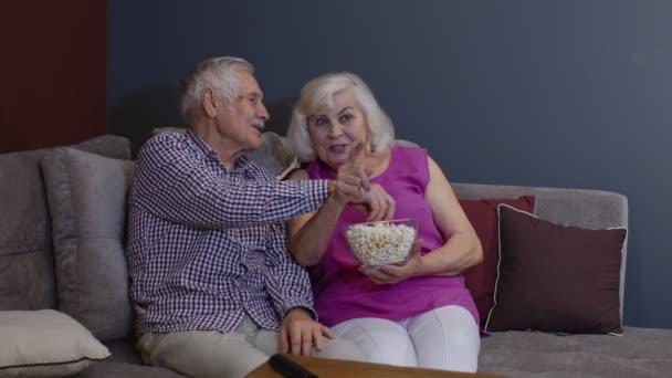 Portré idős pár tévénézés otthon eszik popcorn élvezi film együtt otthon