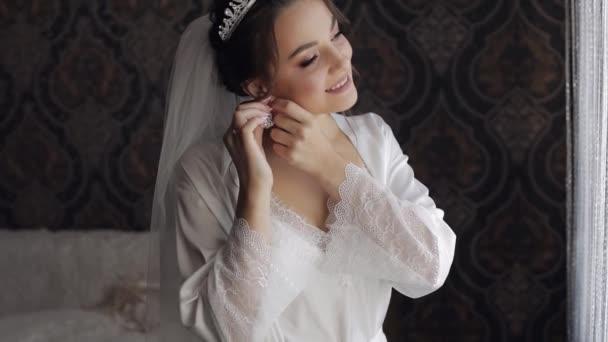 A menyasszony boudoir ruhában fülbevalót visel. Esküvői előkészületek. Nő hálóingben és fátyolban