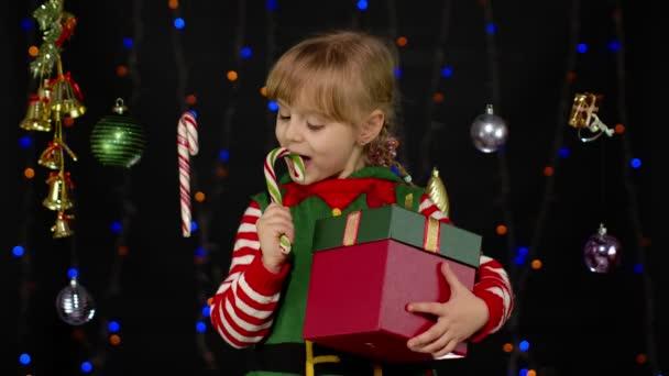 Kind Mädchen im Weihnachtselfen-Helferkostüm leckt Zuckerrohr-Lutscher-Karamell-Bonbons