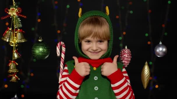 Teen kid girl in Christmas elf Weihnachtsmann Helfer Kostüm zeigt Daumen nach oben auf schwarzem Hintergrund