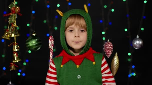 Mädchen im Weihnachtselfen-Helferkostüm tanzt und albert herum. Neujahrsfeier