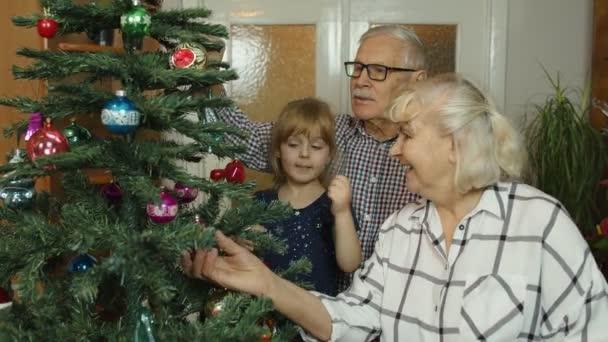 Kindermädchen mit Großelternpaar schmücken künstlichen Tannenbaum im Altersheim