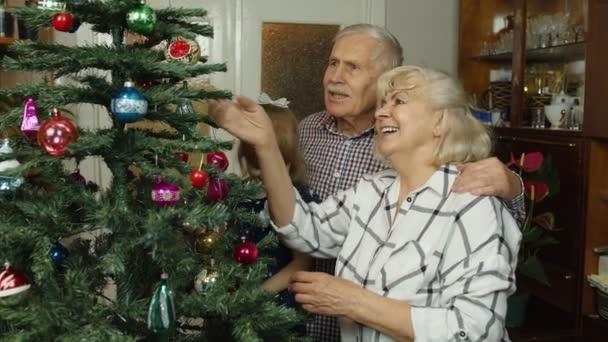 Kind Mädchen mit älteren Großeltern Familie schmücken künstlichen Weihnachtsbaum, Neujahrsferien