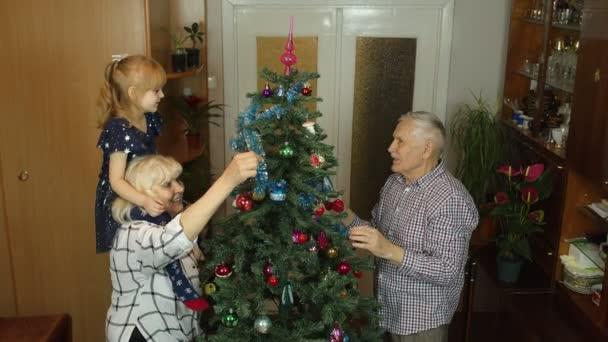 Děvče dívka se starší babičkou a dědečkem zdobí umělý vánoční stromeček s hračkami