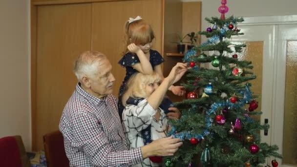 Kleine süße Mädchen mit Senioren Großeltern Familie schmücken künstlichen Weihnachtsbaum zu Hause